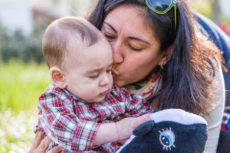 pelo castaño claro: Lindo bebé 6 meses de edad con el pelo marrón claro en pantalones de la camisa a cuadros rojos y beige está recibiendo un beso de mamá hispana Foto de archivo
