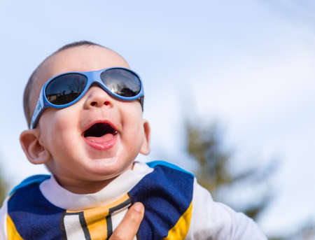 light brown hair: Cute 6 months old baby with Light brown hair in white, blue and brownish long-sleeved shirt wearing blue goggles is embraced and held by his mum: he seems very happy and smiles Stock Photo