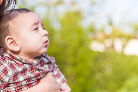 pelo casta�o claro: Vista lateral de 6 meses de edad beb� con el pelo marr�n claro en camisa a cuadros roja y pantalones de color beige, mientras abrazado por su madre Foto de archivo