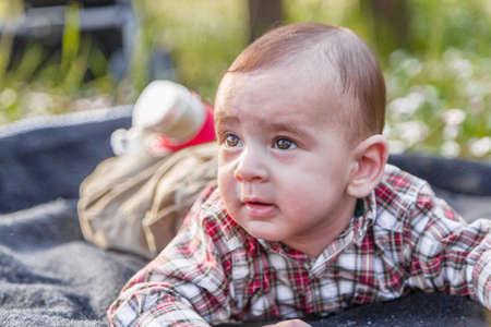 cabello casta�o claro: Lindo beb� de 6 meses de edad con el pelo marr�n claro en camisa a cuadros roja y pantalones beige parece dormida