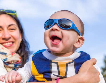 pelo casta�o claro: Lindo beb� 6 meses de edad con el pelo marr�n claro en camisa de manga larga blanca, azul y marr�n que llevaba gafas azules es abrazado y sostenido por su madre: parece muy feliz y sonr�e Foto de archivo