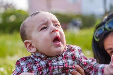 cabello casta�o claro: Lindo beb� 6 meses de edad con el pelo marr�n claro en pantalones de la camisa a cuadros rojos y beige se boquiabierta y mirando hacia arriba mientras abrazado por la madre Foto de archivo