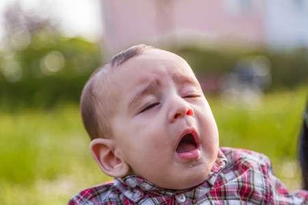 cabello castaño claro: Lindo bebé 6 meses de edad con el pelo marrón claro en camisa a cuadros roja y pantalones de color beige se boquiabierta