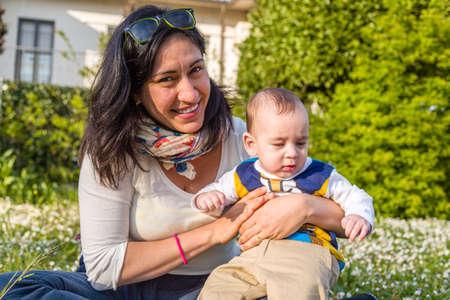 cabello castaño claro: Lindo bebé 6 meses de edad con el pelo marrón claro en camisa de manga larga blanca, azul y marrón es abrazado y sostenido por su madre Foto de archivo