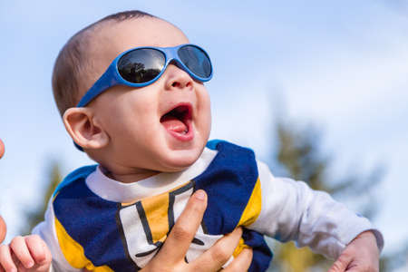 pelo casta�o claro: Cute 6 months old baby with Light brown hair in white, blue and brownish long-sleeved shirt wearing blue goggles is embraced and held by his mum: he seems very happy and smiles Foto de archivo