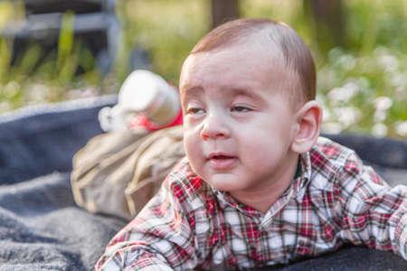 pelo castaño claro: Lindo bebé de 6 meses de edad con el pelo marrón claro en camisa a cuadros roja y pantalones beige parece dormida