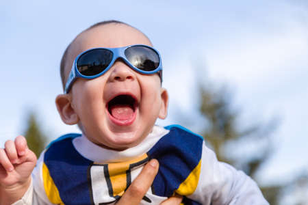 brownish: Cute 6 months old baby with Light brown hair in white, blue and brownish long-sleeved shirt wearing blue goggles is embraced and held by his mum: he seems very happy and smiles Stock Photo