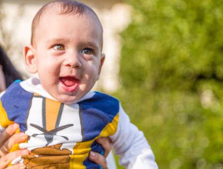 pelo castaño claro: Lindo bebé 6 meses de edad con el pelo marrón claro en camisa de manga larga blanca, azul y marrón es abrazado y sostenido por su madre: parece muy feliz