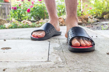 hairy back: Bare feet of boy in black slippers with hairy legs in your back yard