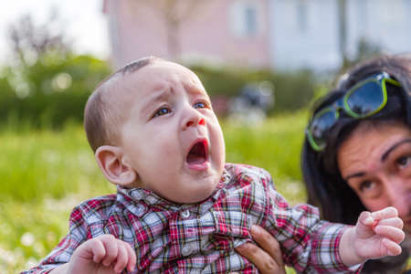 gape: Cute 6 months old baby with Light brown hair in red checkered shirt and beige pants is gaping and looking up while embraced by mother Stock Photo