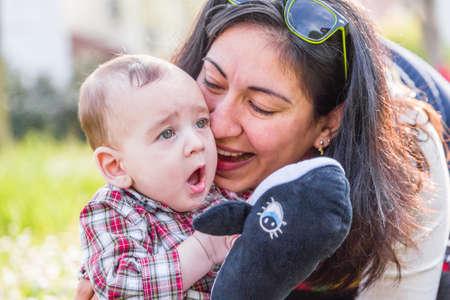 pelo castaño claro: Lindo bebé 6 meses de edad con el pelo marrón claro en pantalones de la camisa a cuadros rojos y beige está escuchando momia hispana