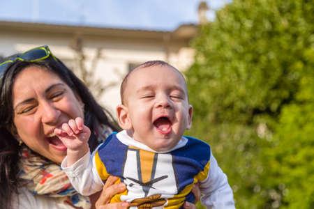 pelo casta�o claro: Lindo beb� 6 meses de edad con el pelo marr�n claro en camisa de manga larga blanca, azul y marr�n es abrazado y sostenido por su madre: parecen muy felices