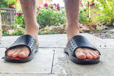 Bare feet of boy in black slippers with hairy legs in your back yard