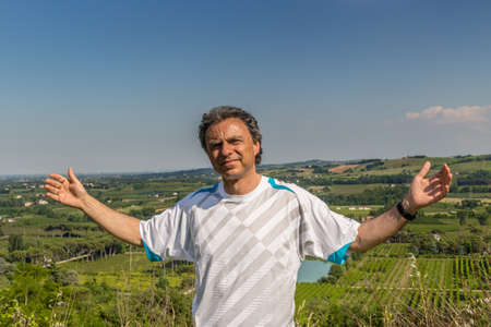 reassuring: Handsome middle-aged man with salt pepper hair dressed with sports shirt is opening his arms in the cultivated fields of Italian countryside: he shows a reassuring look