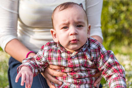 cabello casta�o claro: Lindo beb� de 6 meses de edad con el pelo marr�n claro en camisa a cuadros roja y pantalones beige Foto de archivo