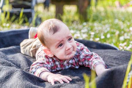 cabello castaño claro: Lindo bebé 6 meses de edad con el pelo marrón claro en pantalones de la camisa a cuadros rojos y beige muestra una mirada pero fanny cara tristemente desesperada Foto de archivo