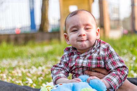 pelo casta�o claro: Cara divertida del beb� lindo 6 meses de edad con el pelo marr�n claro en camisa a cuadros roja y pantalones de color beige: �l est� mordi�ndose los labios y las mejillas puffing