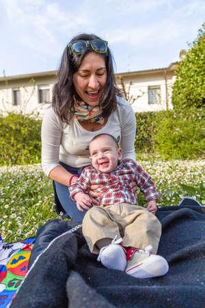 pelo castaño claro: Lindo bebé de 6 meses de edad con el pelo marrón claro en camisa a cuadros roja y pantalones de color beige en manos de la mamá hispana Foto de archivo