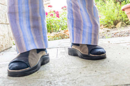 striped pajamas: feet of man in brown slippers with blue socks, blue striped pajamas and gray dressing gown in your back yard