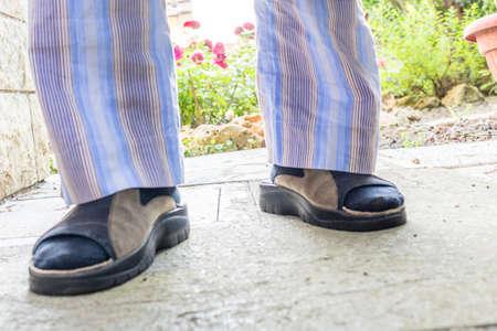 striped pajamas: pies del hombre en zapatillas marrones con calcetines azules, pijama de rayas azules y bata gris en su patio trasero