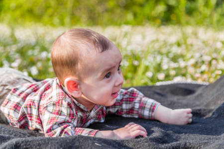 pelo casta�o claro: The innocent happiness of a cute 6 months old baby with Light brown hair in red checkered shirt and beige pants smiling in a city park