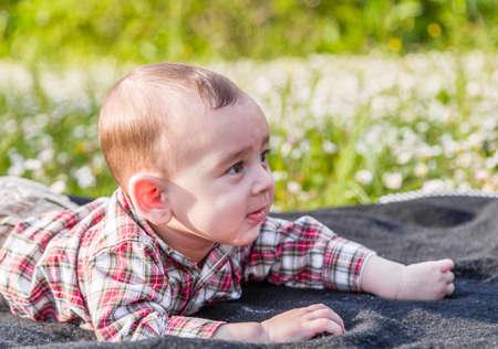 pelo castaño claro: La felicidad inocente de un bebé de 6 meses linda con el pelo marrón claro en camisa a cuadros roja y pantalones beige sonriendo en un parque de la ciudad