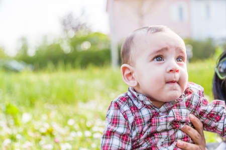 beige lips: Cute 6 months old baby with Light brown hair in red checkered shirt and beige pants is biting his lips, puffing his cheeks and  looking up while embraced by mother