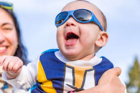 brownish: Cute 6 months old baby with Light brown hair in white, blue and brownish long-sleeved shirt wearing blue googles is embraced and held by his mum: he seems very happy and smiles gaping