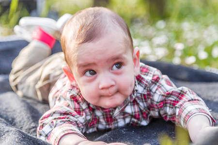 cabello casta�o claro: Cara divertida del beb� lindo 6 meses de edad con el pelo marr�n claro en camisa a cuadros roja y pantalones de color beige: �l est� mordi�ndose los labios y las mejillas puffing