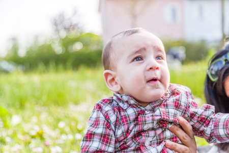 light brown hair: Funny face of cute 6 months old baby with Light brown hair in red checkered shirt and beige pants: hes biting his lips and puffing cheeks