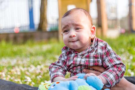 cabello castaño claro: Cara divertida del bebé lindo 6 meses de edad con el pelo marrón claro en camisa a cuadros roja y pantalones de color beige: él está mordiéndose los labios y las mejillas puffing