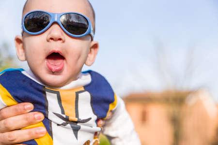 cabello casta�o claro: Divertida del beb� de 6 meses de edad con el pelo marr�n claro en camisa de manga larga blanca, azul y marr�n que llevaba gafas azules es abrazado y sostenido por su madre: parece muy feliz y abre la boca