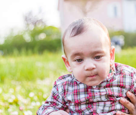puffing: Cute 6 months old baby with Light brown hair in red checkered shirt and beige pants is biting his lips, puffing his cheeks and  looking down while embraced by mother