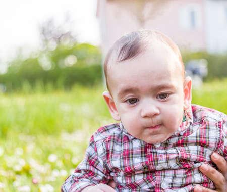 pantalones abajo: Lindo bebé de 6 meses de edad con el pelo marrón claro en camisa a cuadros roja y pantalones de color beige se mordía los labios, hinchando las mejillas y mirando hacia abajo mientras abrazado por la madre