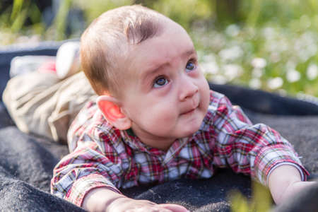 beige lips: Funny face of cute 6 months old baby with Light brown hair in red checkered shirt and beige pants: hes biting his lips and puffing cheeks