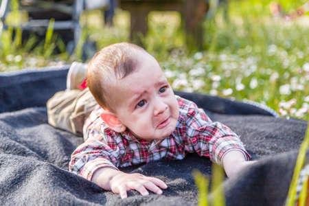 cabello casta�o claro: Lindo beb� 6 meses de edad con el pelo marr�n claro en pantalones de la camisa a cuadros rojos y beige muestra una mirada pero fanny cara tristemente desesperada Foto de archivo
