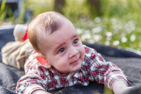 cabello castaño claro: Lindo bebé de 6 meses de edad con el pelo marrón claro en camisa a cuadros roja y pantalones beige muestra Lookk serena