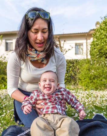 cabello casta�o claro: Lindo beb� de 6 meses de edad con el pelo marr�n claro en camisa a cuadros roja y pantalones de color beige en manos de la mam� hispana Foto de archivo