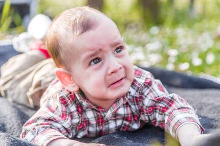 pelo casta�o claro: Lindo beb� 6 meses de edad con el pelo marr�n claro en pantalones de la camisa a cuadros rojos y beige muestra una mirada pero fanny cara tristemente desesperada Foto de archivo