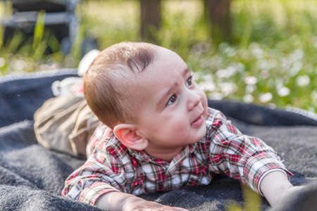 cabello castaño claro: La felicidad inocente de un bebé de 6 meses linda con el pelo marrón claro en camisa a cuadros roja y pantalones beige sonriendo en un parque de la ciudad