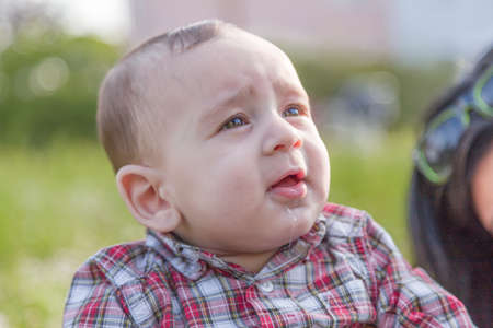 pelo casta�o claro: La felicidad inocente de un beb� de 6 meses linda con el pelo marr�n claro en camisa a cuadros roja y pantalones beige sonriendo en un parque de la ciudad