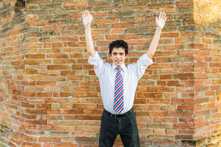 arma: Handsome Caucasian boy wearing a white shirt and a regimental tie with red, fuchsia, orange, blue, indigo and white stripes is raising arms in front of a brick wall at sunset