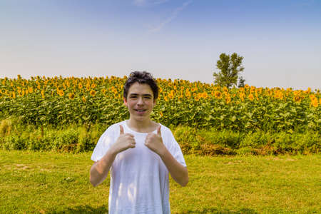 pimples: Natural and healthy living - Caucasian boy with acne and pimples smiling an making success sign with both thumbs up  in front of a field of sunflowers