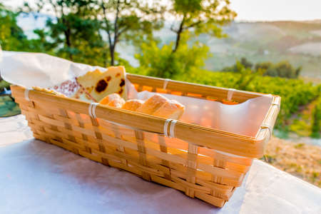 farmlands: dinner in the country – bread basket on a table with vineyards, farmlands and green vegetation of the countryside in the background Stock Photo