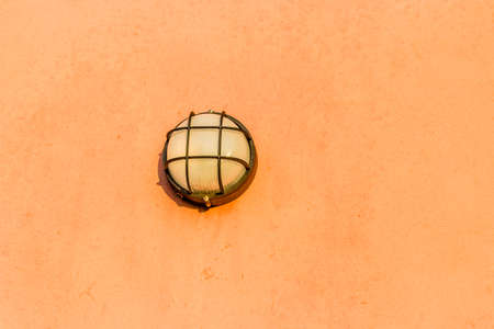 wall sconce: wall lights with lattice on orange plaster of the outer wall of country house Stock Photo