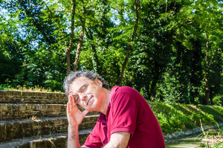 charisma: Charismatic and handsome Caucasian sportsman of forty with grey hair wearing red polo shirt and dark linen trousers holds his head while sitting on the ancient medieval steps of Mill Canal in Emilia Romagna in Italy