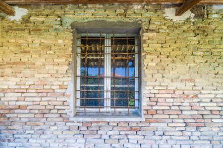 dilapidated wall: iron bars window in dilapidated brick wall Stock Photo