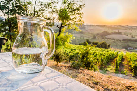 farmlands: dinner in the country - jug of clear, fresh and sweet water on a table with vineyards, farmlands and green vegetation of the countryside in the background Stock Photo