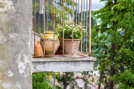 rejas de hierro: balcón viejo que desmenuza con macetas de flores y barras de hierro en Italia