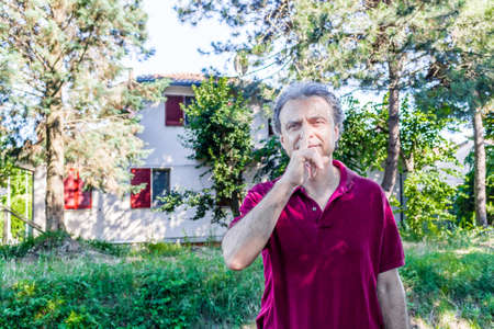 charismatic: Charismatic and handsome Caucasian sportsman of forty with grey hair wearing red polo shirt and dark linen trousers invites you to be quiet with a finger over his lips in a park in Emilia Romagna in Italy